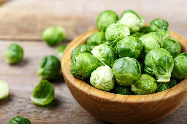 fresh organic brussels sprouts raw in a plate on wooden background. stock photo