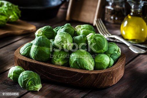 Fresh organic Brussels sprouts in a wooden tray shot on rustic wooden kitchen table. This vegetable is considered a healthy salad ingredient. Predominant colors are green and brown. Low key DSRL studio photo taken with Canon EOS 5D Mk II and Canon EF 100mm f/2.8L Macro IS USM