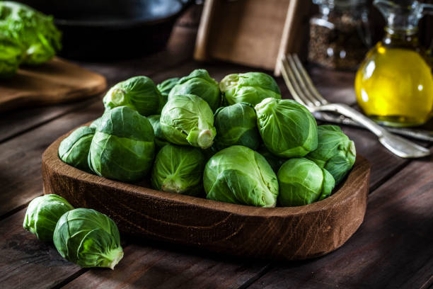 Fresh organic Brussels sprouts shot on rustic wooden table stock photo