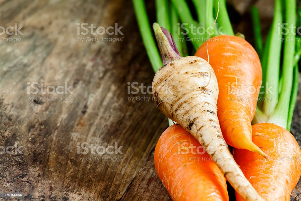 Fresh organic carrots and parsnips on old wooden table, selective...