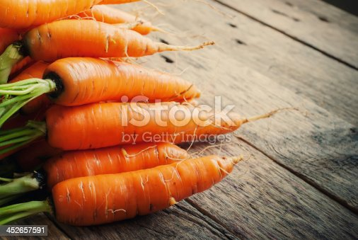 istock Fresh Organic Carrots in a basket on wooden background, rustical 452657591