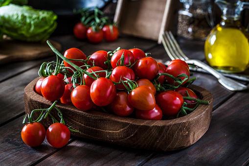 Fresh organic cherry tomatoes in a wooden tray shot on rustic wooden kitchen table. This vegetable is considered a healthy salad ingredient. Predominant colors are red and brown. Low key DSRL studio photo taken with Canon EOS 5D Mk II and Canon EF 100mm f/2.8L Macro IS USM
