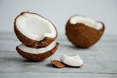 broken fresh organic coconut on rustic wooden grey background
