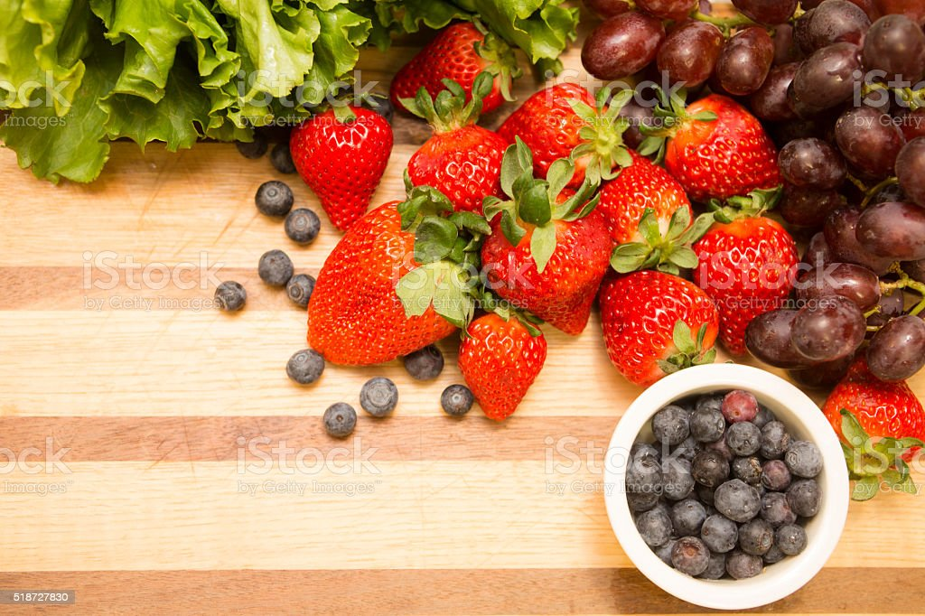 Fresh, organic fruits on wooden cutting board. Strawberries, grapes, blueberries. stock photo