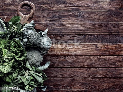 Fresh organic, pesticide free, garden grown, leafy green healthy vegetables in an antique wooden carved bowl on an old teak wood paneled table background, shadow atmospheric rustic retro styled, grunge mood, with good copy space at the right of the image. Vegetables include broccoli, spinach and bok choy.