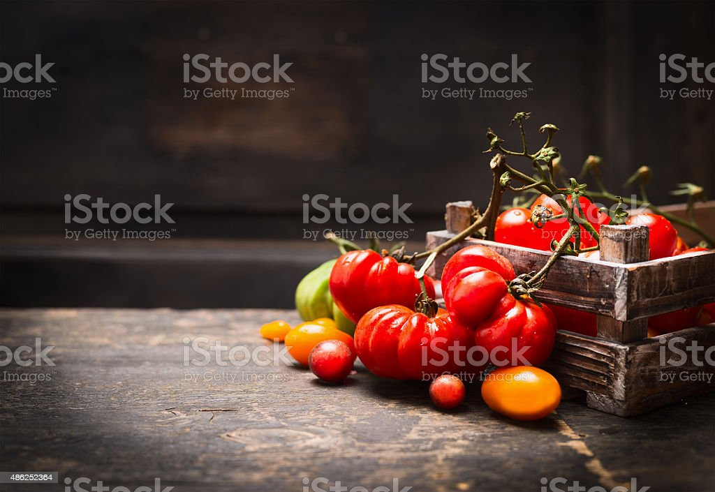 Fresh organic garden tomatoes in vintage box over wooden background. stock photo