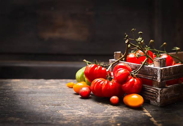 frische bio-garten, tomaten in vintage-box über hölzerne hintergrund. - geschlossene küchen stock-fotos und bilder