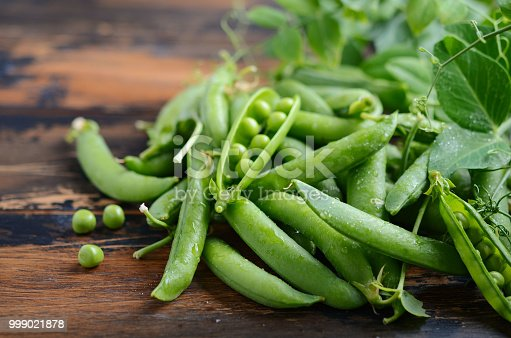 Fresh organic green peas on rustic wooden background, selective focus.