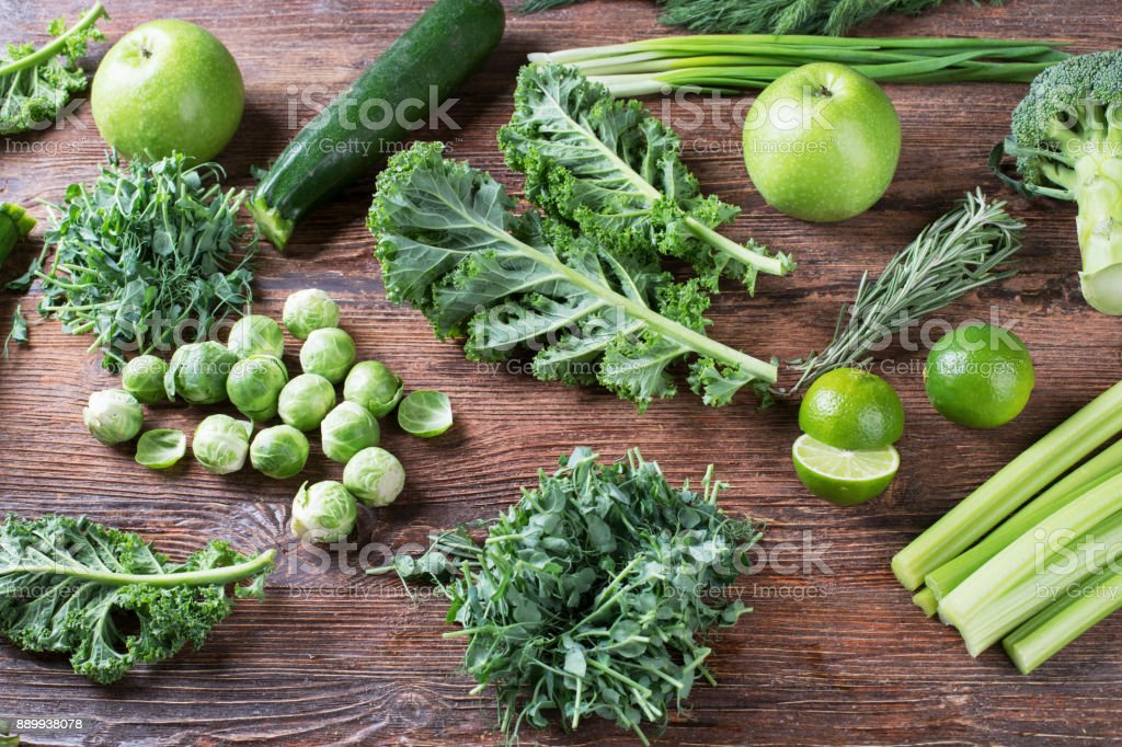 Fresh organic green vegetables  on wooden background. stock photo