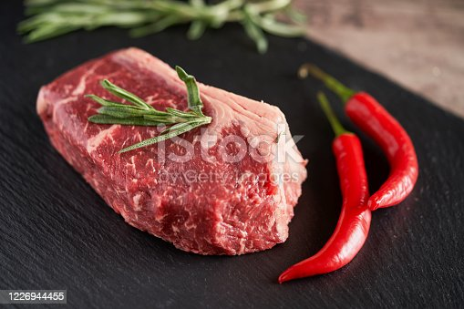 808351094 istock photo Fresh, organic juicy New York steak on a slate plate with two pods of red chili peppers and a rosemary evening. Premium quality meat steaks. Grill and BBQ 1226944455