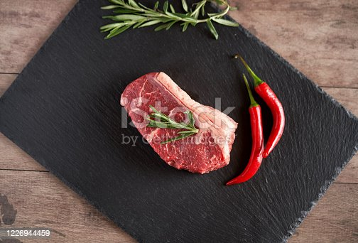 808351094 istock photo Fresh, organic juicy New York steak on a slate plate with two pods of red chili peppers and a rosemary evening. Premium quality meat steaks. Grill and BBQ 1226944459