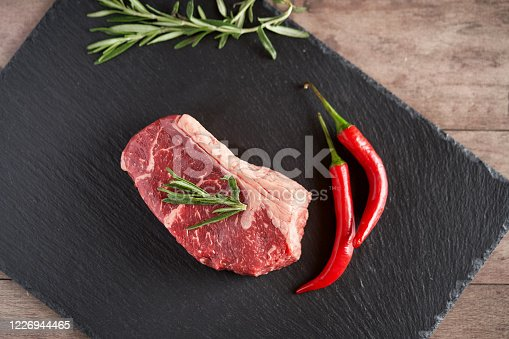808351094 istock photo Fresh, organic juicy New York steak on a slate plate with two pods of red chili peppers and a rosemary evening. Premium quality meat steaks. Grill and BBQ 1226944465