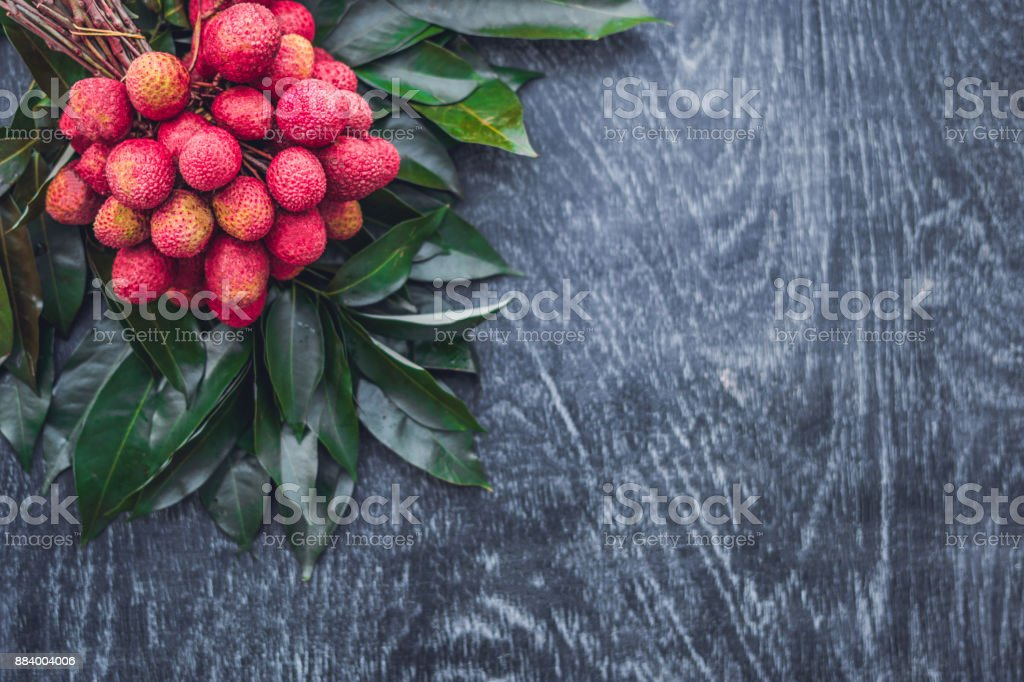 Fresh organic lychee fruit and lychee leaves on a rustic wooden background stock photo