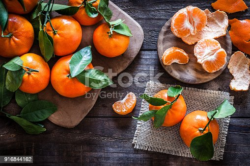 Top view of fresh organic mandarins on rustic wooden table. One mandarin is peeled. Predominant colors are orange and brown. DSRL studio photo taken with Canon EOS 5D Mk II and Canon EF 100mm f/2.8L Macro IS USM