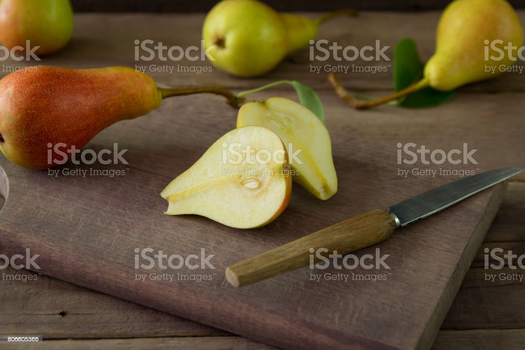 Fresh organic pears and one cut pear on wooden plank stock photo