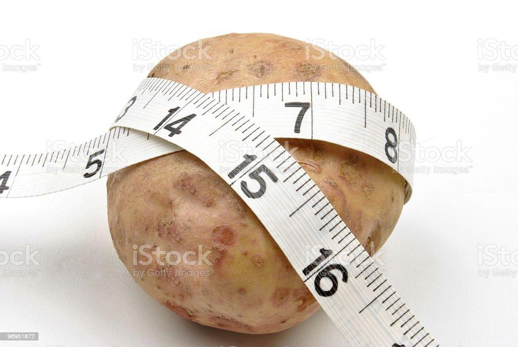 fresh organic potato and inch tape measure royalty-free stock photo