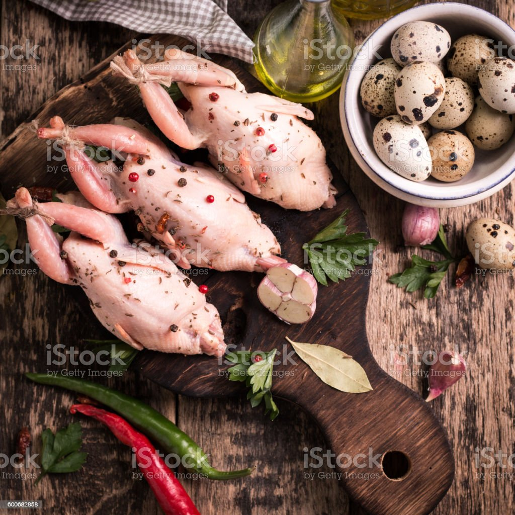 Fresh organic quails on vintage wooden table, healthy food stock photo
