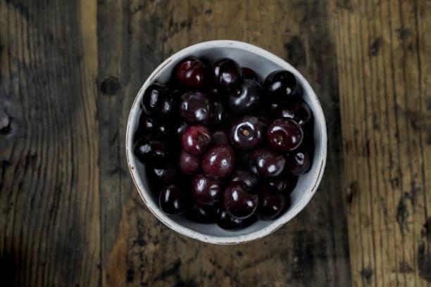cerezas negras frescas orgánicas maduras en un tazón blanco sobre una mesa de madera rústica - negras maduras fotografías e imágenes de stock