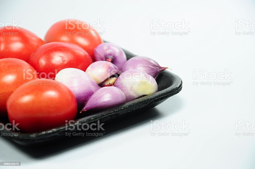 Fresh organic shallots and red tomatoes on black plastic tray royalty-free stock photo