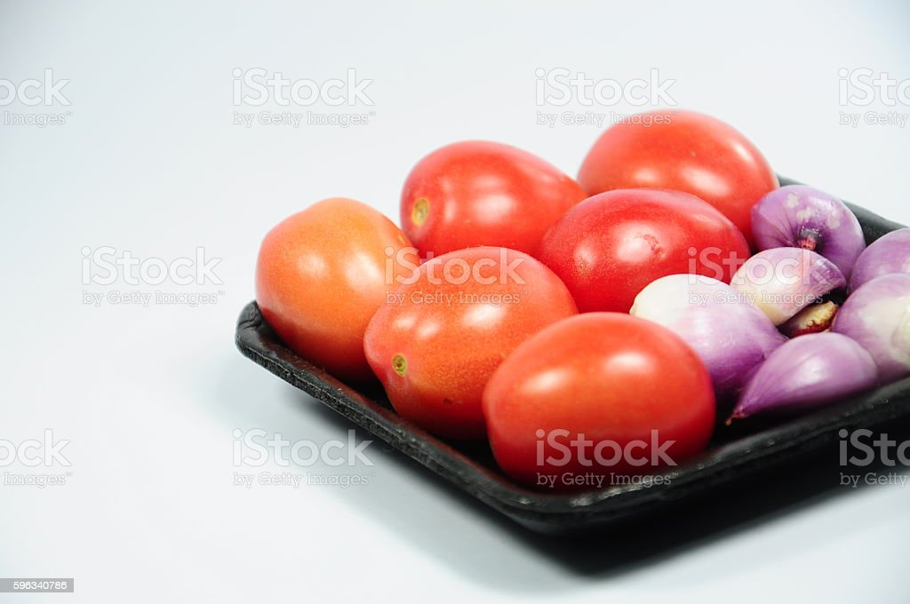 Fresh organic shallots and red tomatoes on the black tray royalty-free stock photo