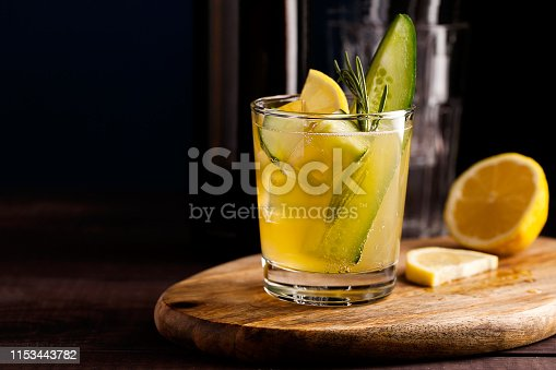 Fresh organic summer cocktail made with sour ginger craft beer or kombucha tea with cucumber and lemon on wooden background. Drink on the bar table with copy space. Trendy vegan refreshing beverage. Horizontal orientation