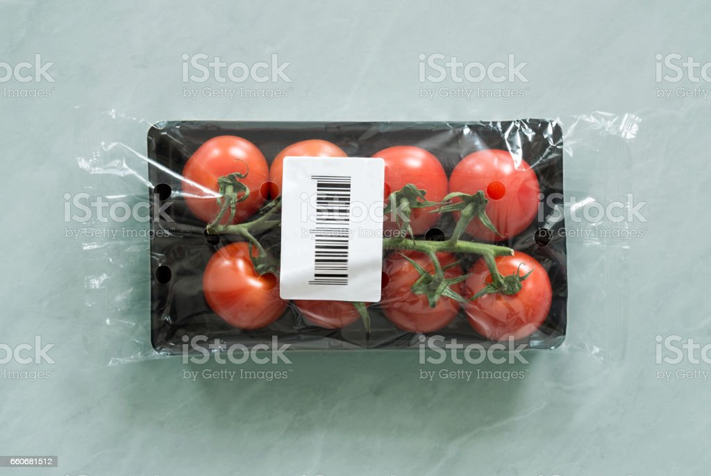 Fresh organic tomatoes inside of market package with bar code label stock photo