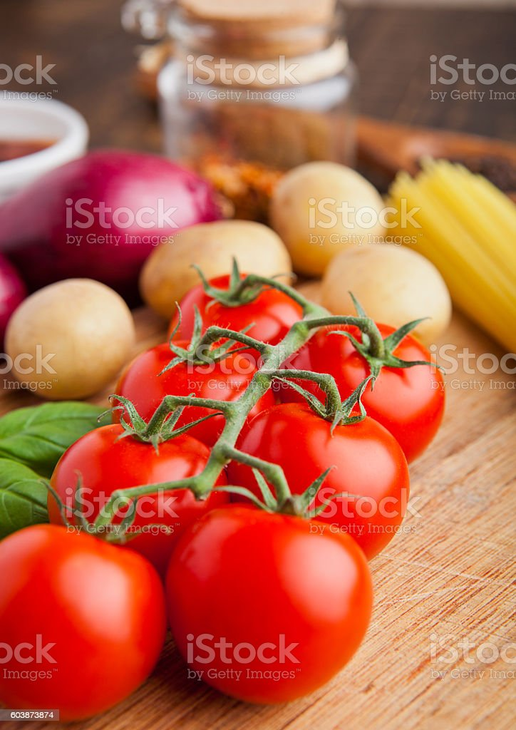 Fresh organic tomatoes with vegetables on wooden board stock photo