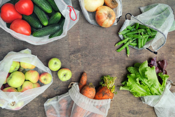 Fresh organic vegetables, fruits and greens in reusable recycled mesh produce bags on wooden background with copy space. Zero waste shopping concept. No single-use plastic. Fresh organic vegetables, fruits and greens in reusable recycled mesh produce bags on wooden background with copy space. Zero waste shopping concept. No single-use plastic. environmental consciousness stock pictures, royalty-free photos & images