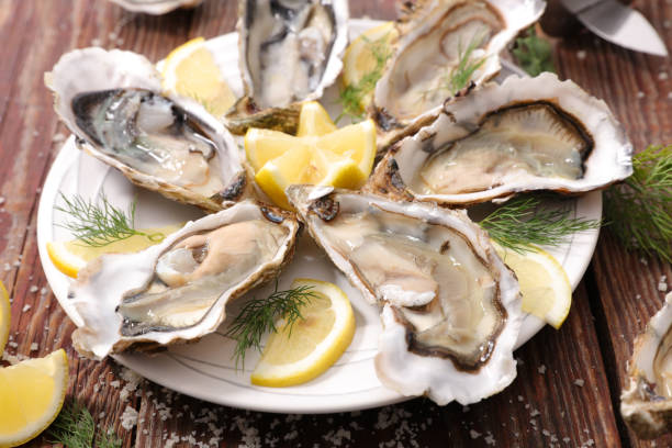 fresh oyster with lemon - oyster stock pictures, royalty-free photos & images