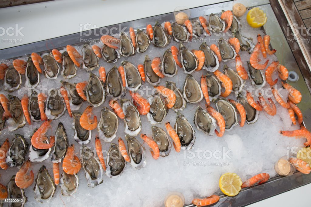 Fresh oyster with shrimps on ice at fish market stock photo