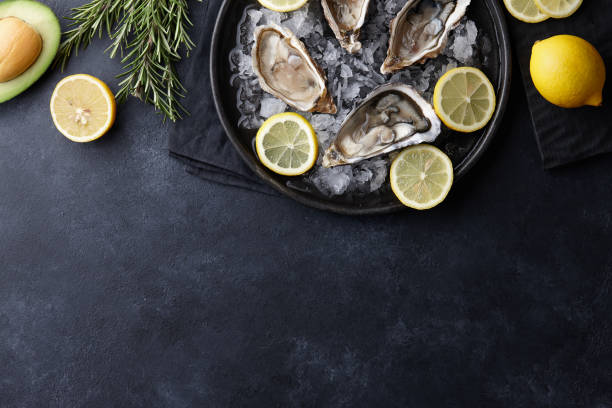 fresh oysters in a plate with ice on black background - oyster stock pictures, royalty-free photos & images