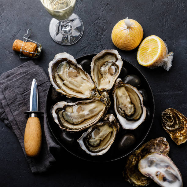 fresh oysters with lemon and champagne on stones on dark background - oyster stock pictures, royalty-free photos & images