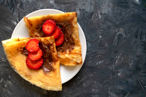 Fresh pancakes with chocolate paste and strawberry on gray background with copy space stock photo