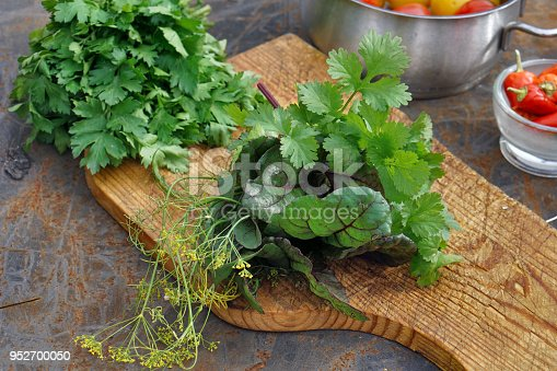 istock Fresh parsley, dill,  mangold, coriander on wooden board and Tomatoes and chile on iron backgrownd. 952700050