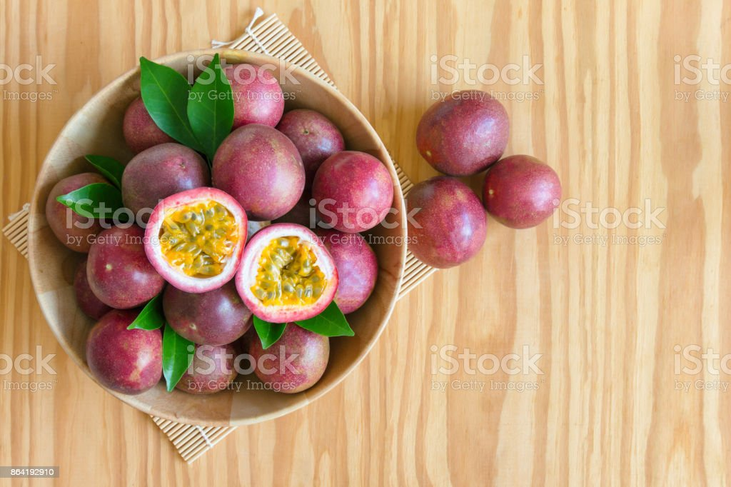 Fresh passion fruit in wood bowl on wood table in top view flat lay with copy space for background or wallpaper. Ripe passion fruit so sweet and sour. Tropical fruit. royalty-free stock photo