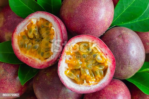 istock Fresh passion fruit on wood table in top view flat lay for background or wallpaper. Ripe passion fruit so delicious sweet and sour. Close up on a half of passion fruit in macro concept.Tropical fruit. 860079962