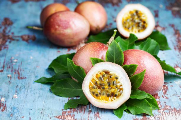 fruit de la passion frais avec des feuilles originales sur fond en bois bleu - fruit de la passion photos et images de collection