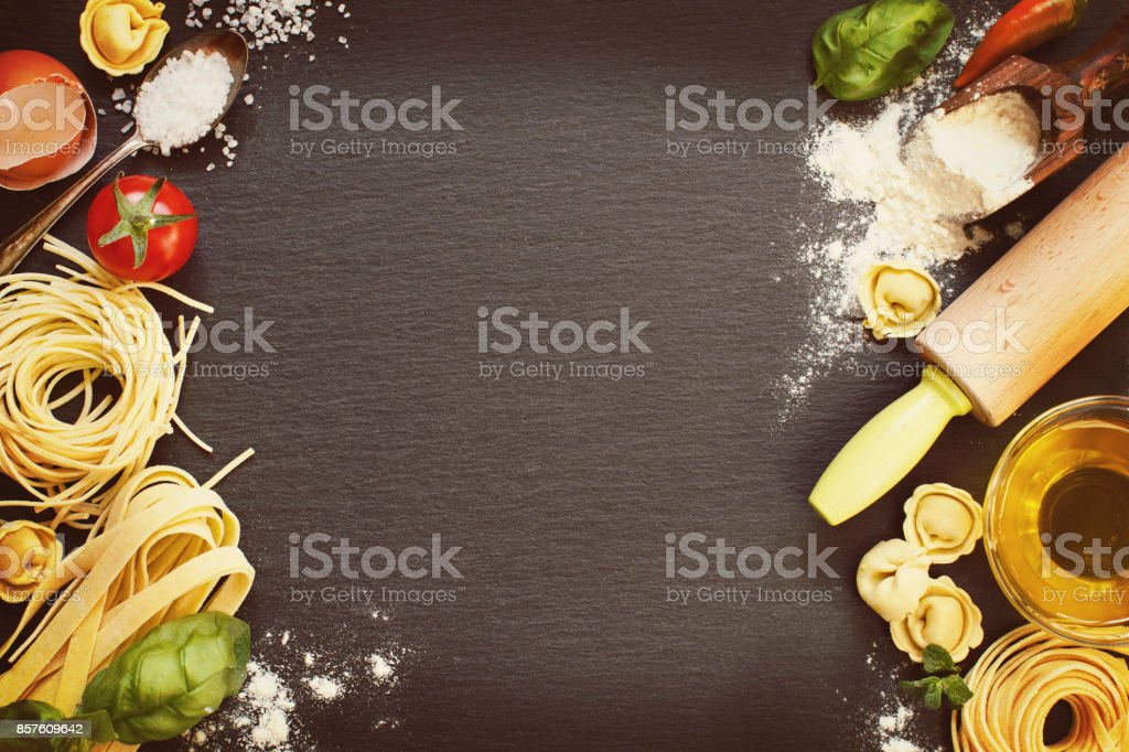 Fresh pasta and ingredients on a dark board stock photo