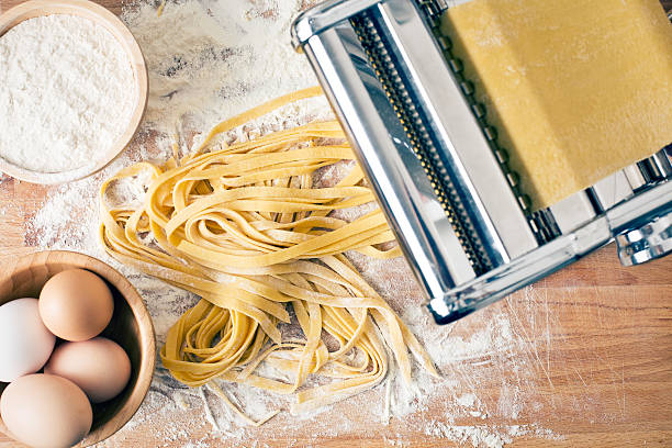 fresh pasta and pasta machine fresh pasta and pasta machine on kitchen table tagliatelle stock pictures, royalty-free photos & images