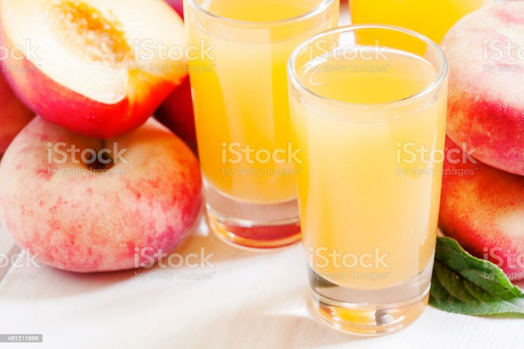 Fresh peach juice with fruits on a white wooden background stock photo
