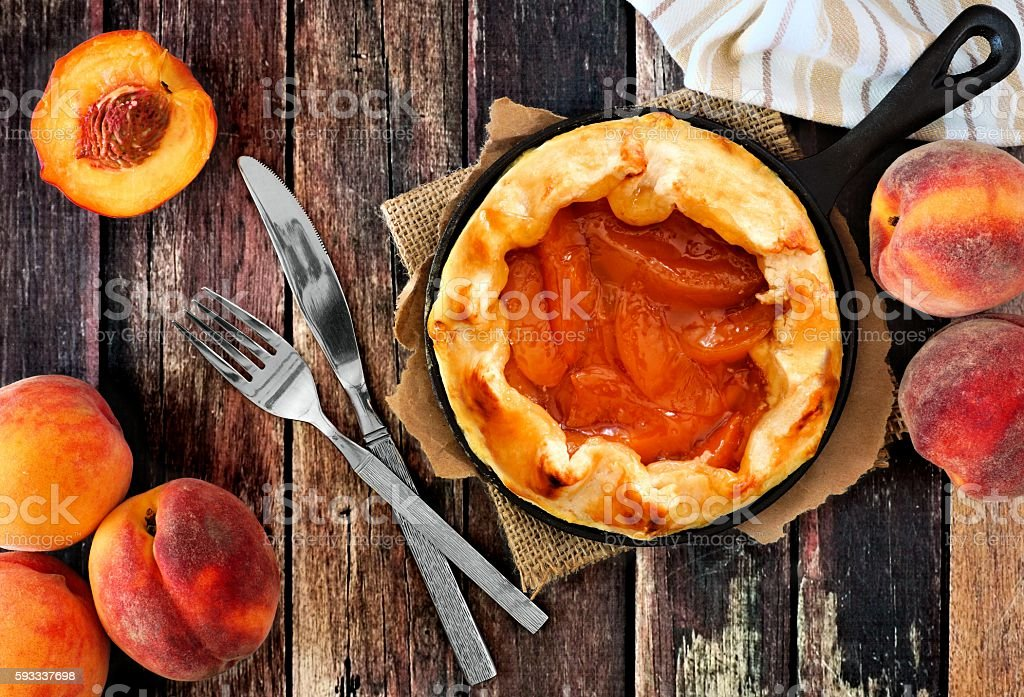 Fresh peach tart in cast iron skillet over rustic wood stock photo