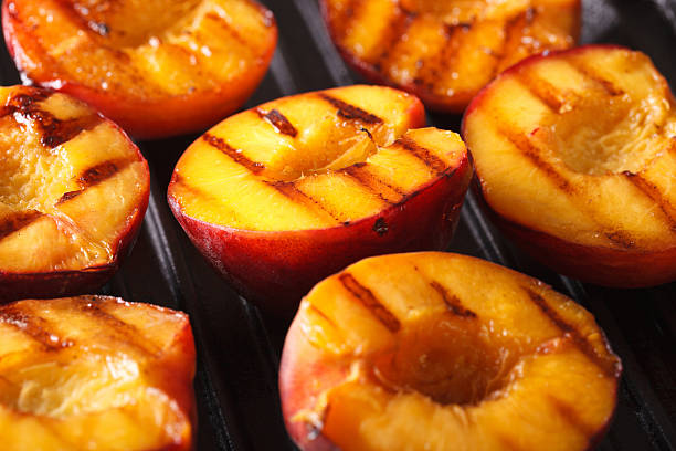 fresh peaches on grill macro. horizontal - жареный на гриле стоковые фото и изображения