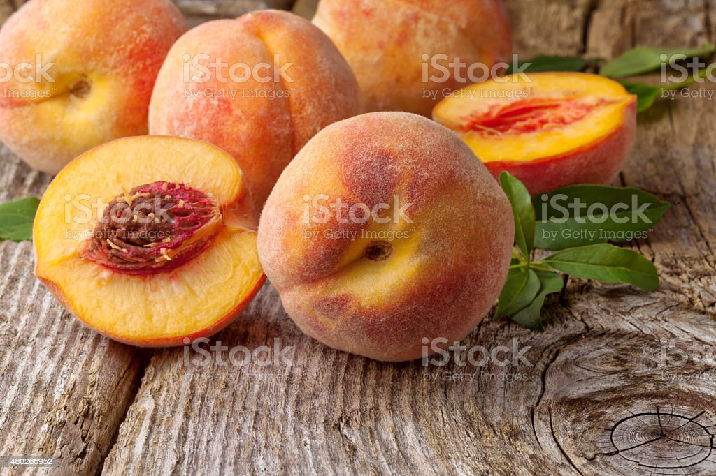Fresh peaches on wooden background stock photo