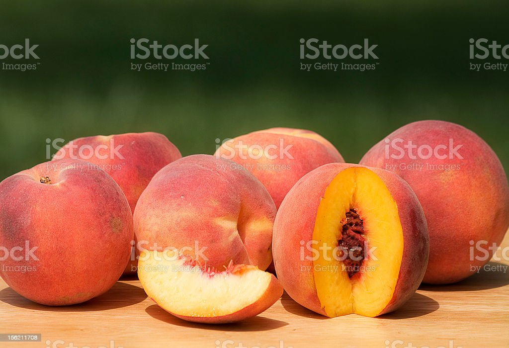 Fresh peaches sitting on a picnic table royalty-free stock photo