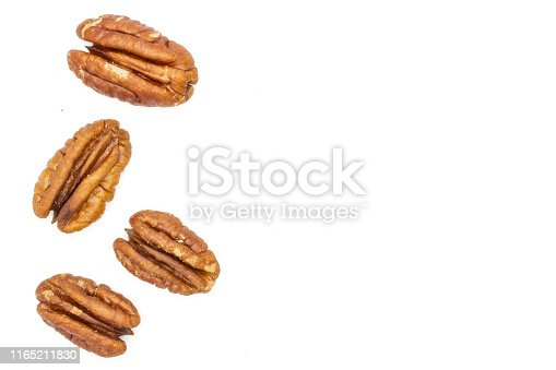 Group of four whole fresh brown pecan nut half copyspace on right flatlay isolated on white background