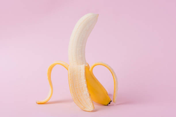 fresh peeled banana on pink background - peeled stock photos and pictures