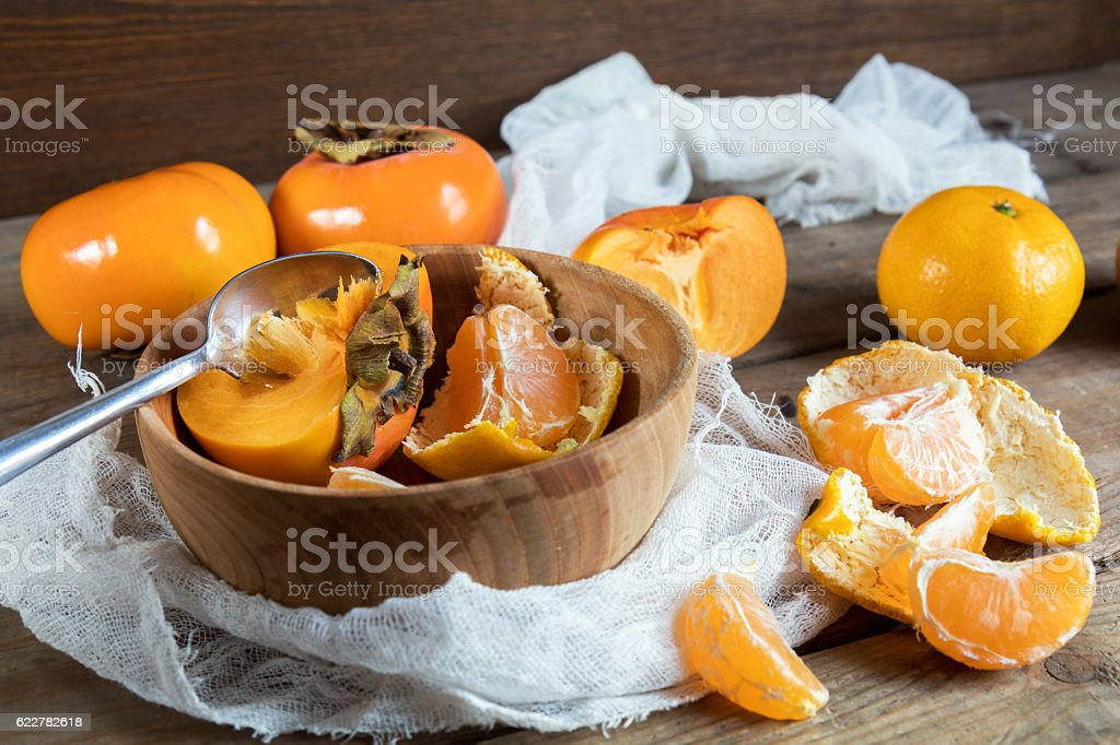 Fresh persimmons and tangerines fruits in bowl royalty-free stock photo