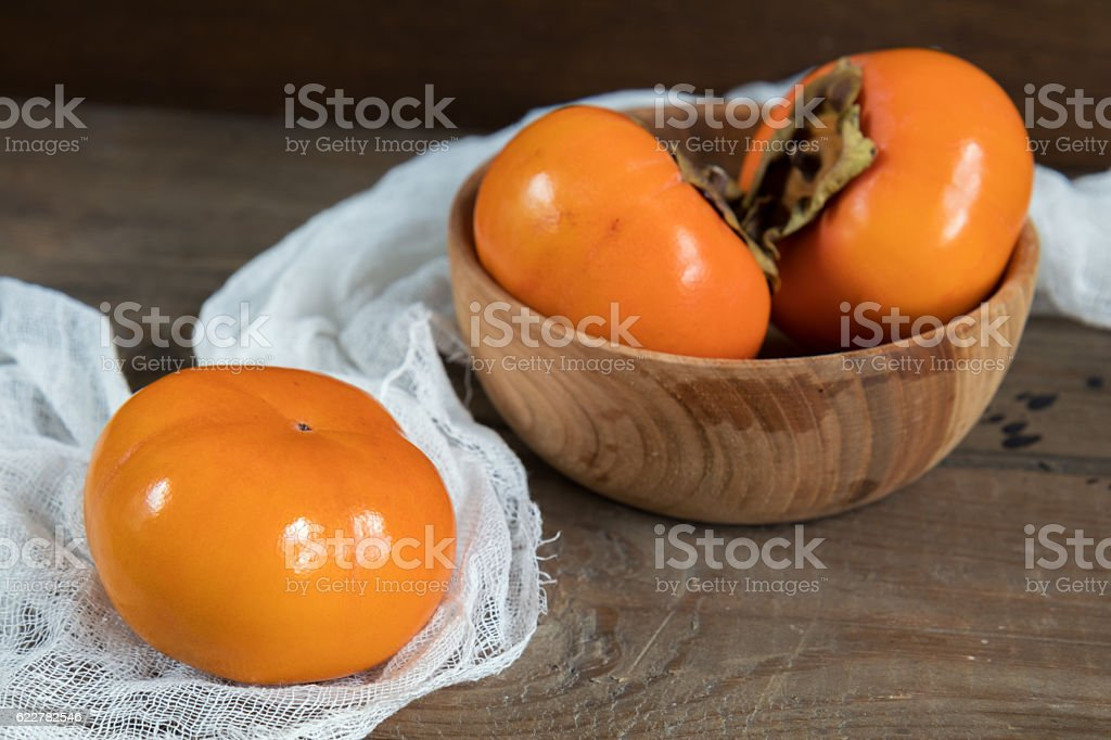 Fresh persimmons fruit in bowl stock photo