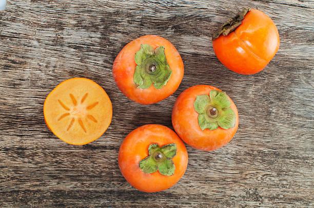 fresh persimmons on a wooden table - sharonfrucht stock-fotos und bilder