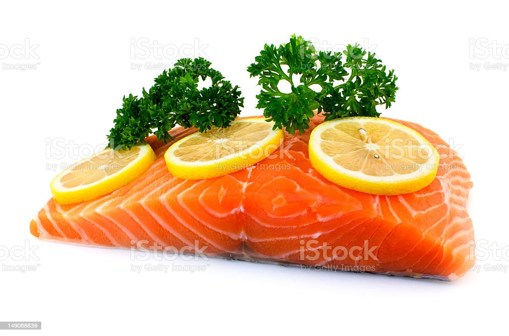 A fresh piece of salmon with slices of lemon and parsley royalty-free stock photo